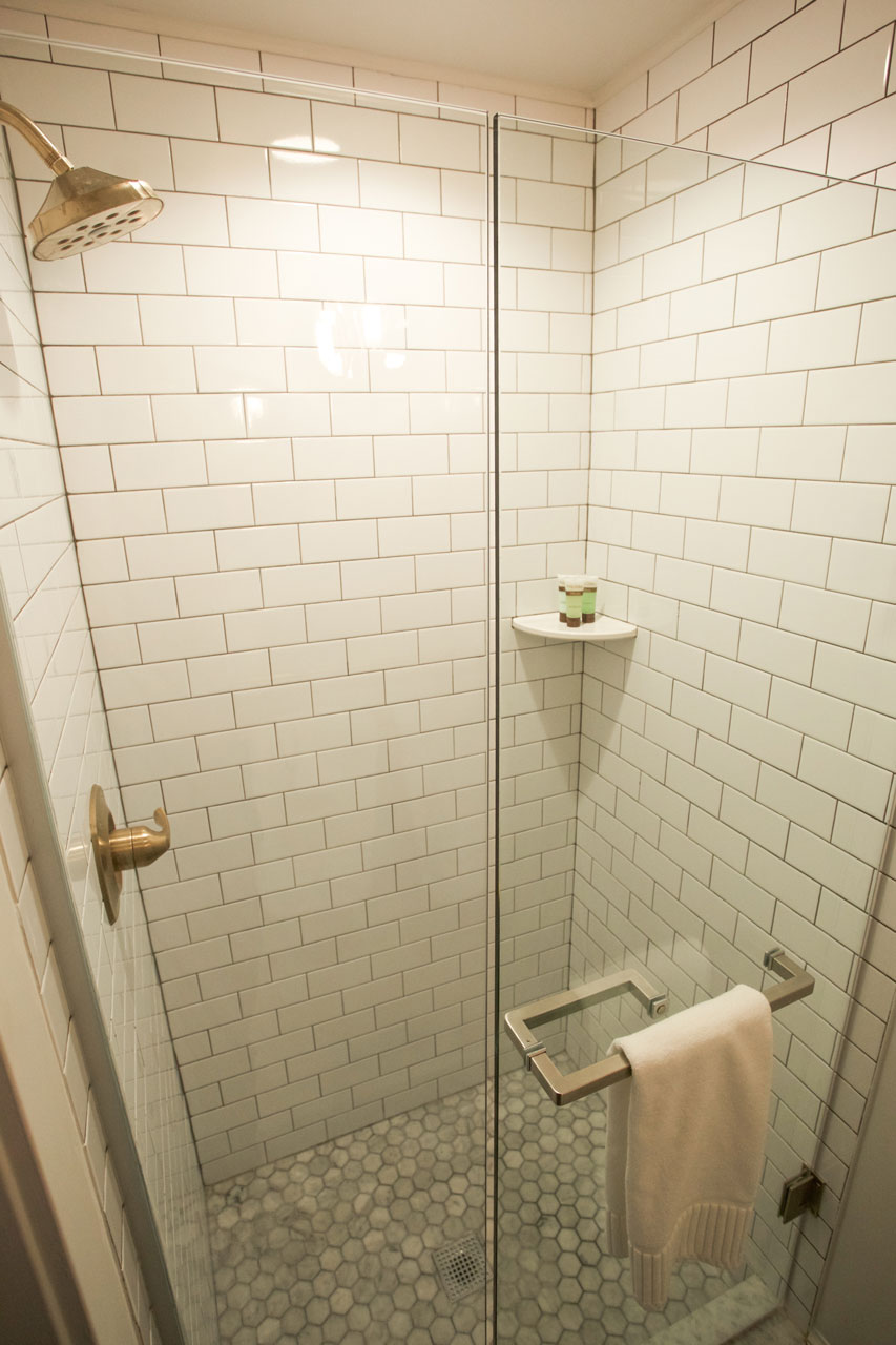 large standing shower with gold hardware and subway title