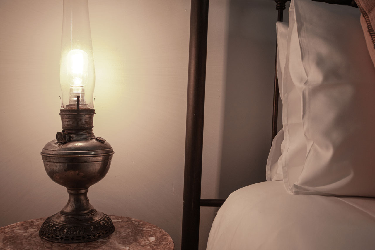 antique lamp that looks like a gas lantern next to hotel bed