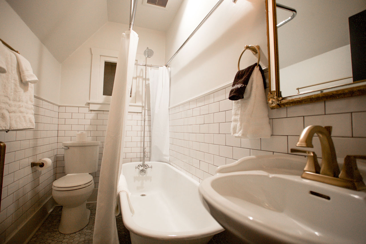 footed bath tub with shower in a large personal hotel barthroom