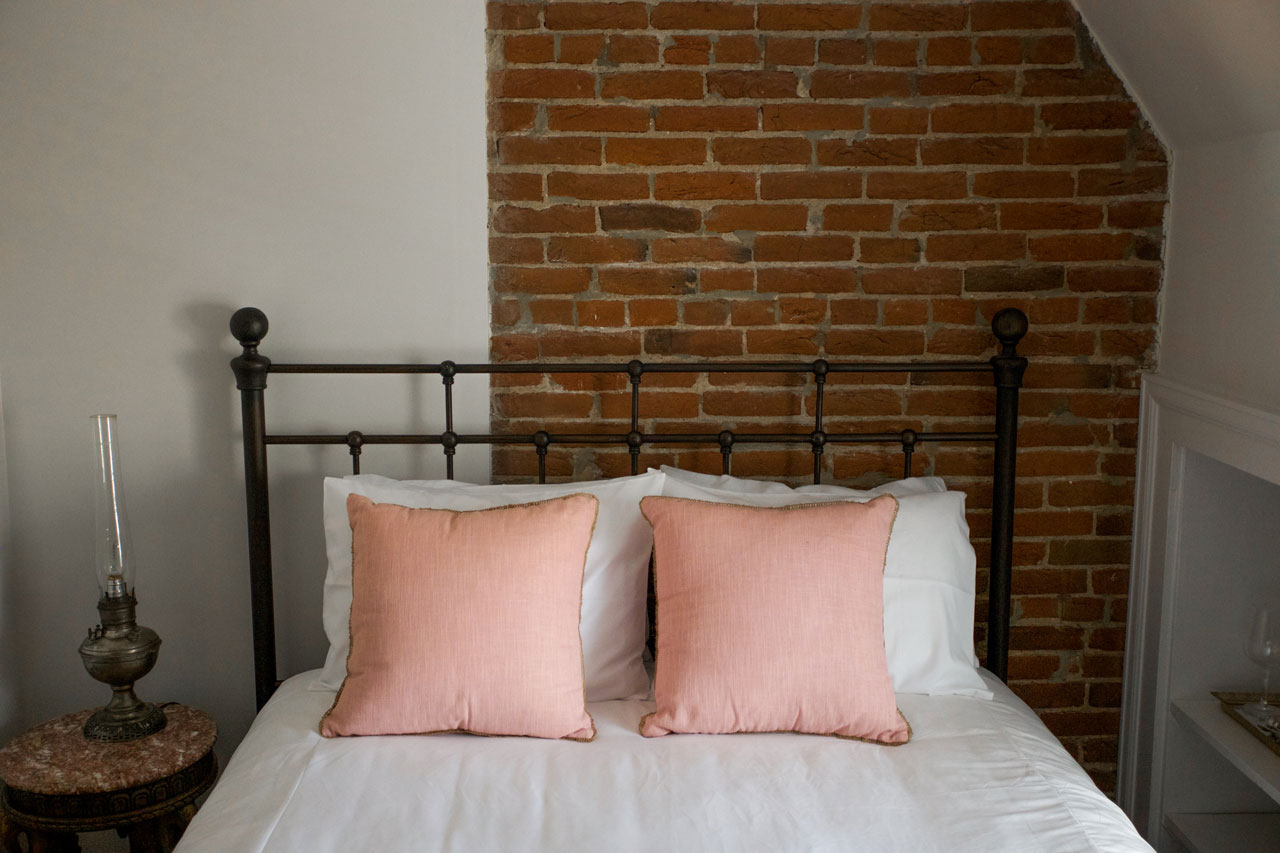 Red Rocks room bed with exposed brick wall